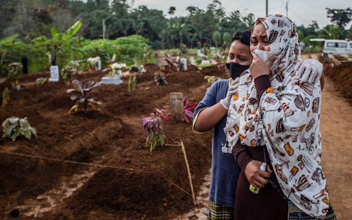 mother mourns with her son during her mother's funeral at the Mulyaharja cemetery for Covid-19 coronavirus victims, in Bogor, West Java - AFP