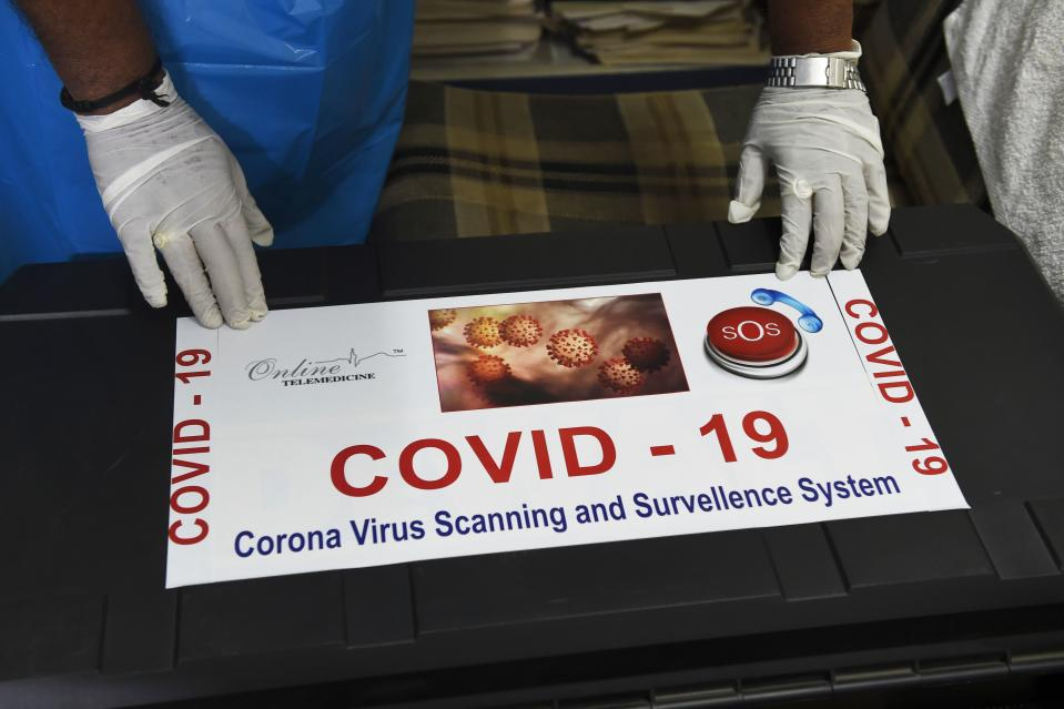 Team member of Ragesh Shah, a scientist and founder of Online Telemedicine Research Institute, puts a sticker on a kit prepared for the coronavirus scanning and surveillance system, in Ahmedabad on March 6, 2020. - India has reported 31 cases of the virus that has killed more than 3,300 people and infected nearly 100,000 worldwide after it emerged in the Chinese city of Wuhan in December. (Photo by SAM PANTHAKY / AFP) (Photo by SAM PANTHAKY/AFP via Getty Images)