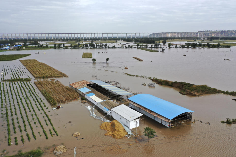 In this photo released by Xinhua News Agency, an aerial photo shows an overflowing Yellow River near the Lianbo Village in Hejin City, northern China's Shanxi Province, Sunday, Oct. 10, 2021. (Zhan Yan/Xinhua via AP)