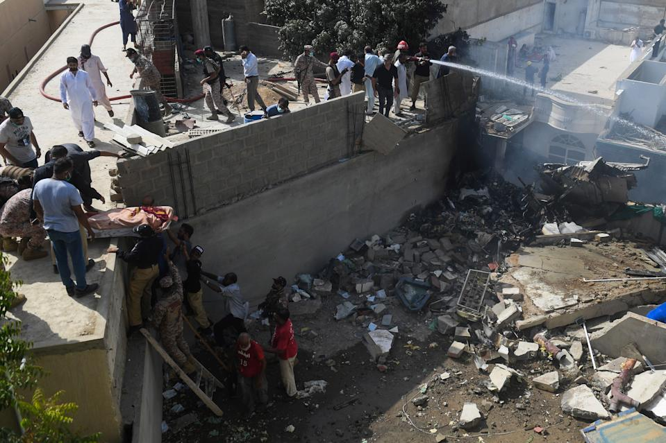 Rescue workers move a body from the site after a Pakistan International Airlines aircraft after crashed at a residential area in Karachi on May 22, 2020. - A Pakistan passenger plane with more than 100 people believed to be on board crashed in the southern city of Karachi on May 22, the country's aviation authority said. (Photo by Asif HASSAN / AFP) (Photo by ASIF HASSAN/AFP via Getty Images)