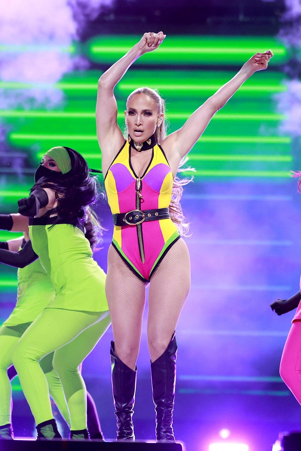 <p>J Lo stayed in her Fausto Puglisi for Roberto Cavalli choker and swapped her minidress for this belted, neon colorblock bodysuit with the same knee-high boots.</p>