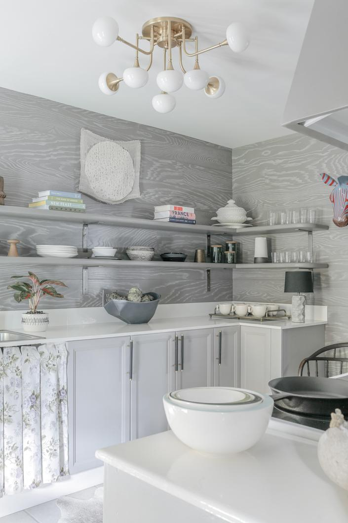 """<div class=""""caption""""> <strong>AFTER</strong>: Maryline achieved her vision of a """"rustic, glam, Victorian"""" kitchen by integrating a mix of high/low materials. Opting to refurbish used cabinets purchased for $500 and construct inexpensive countertops left room in the budget for splurging on the wood-paneled wall treatment, and the eye catching <a href=""""https://www.hvlgroup.com/Product/4708-AGB"""" rel=""""nofollow noopener"""" target=""""_blank"""" data-ylk=""""slk:light fixture"""" class=""""link rapid-noclick-resp"""">light fixture</a>. </div>"""