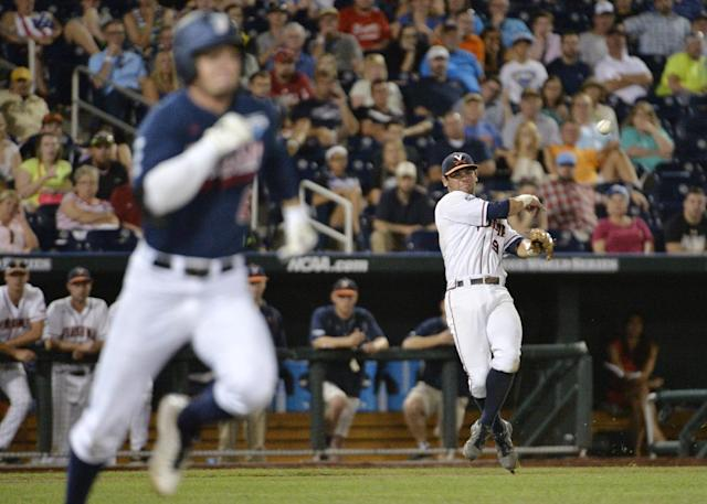 Virginia third baseman Kenny Towns (9) handles a ground ball as Vanderbilt right fielder Rhett Wiseman runs safely to first base in the seventh inning of game one of the best-of-three NCAA baseball College World Series finals in Omaha, Neb., Monday, June 23, 2014. (AP Photo/Ted Kirk)