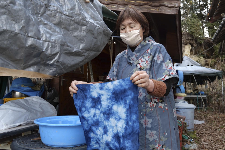 In this image from video, Yoshiko Ogura, 73, holds up a handkerchief dyed without using any chemical substances in front of her studio in Minamisoma, Fukushima Prefecture, northeastern Japan, on Feb. 20, 2021. After the Fukushima nuclear plant disaster a decade ago, nearby farmers weren't allowed to grow crops for two years because of radiation. After the restriction was lifted, two farmers in the town of Minamisoma found an unusual way to rebuild their lives and help their destroyed community. Kiyoko Mori and Ogura planted indigo and soon began dying fabric with dye produced from the plants. (AP Photo/Chisato Tanaka)
