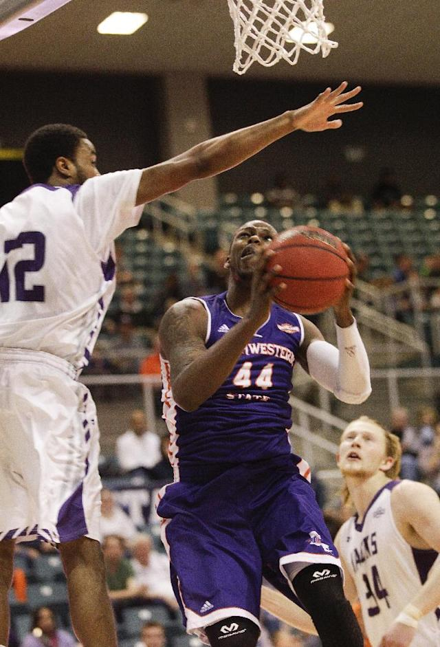Northwestern State's Gary Stewart (44) drives to the basket as Stephen F. Austin's Dallas Cameron (12) attempts to block his shot during the first half of an NCAA college basketball game in the semifinal round of the Southland Conference tournament Friday, March 14, 2014, in Katy. (AP Photo/Bob Levey)