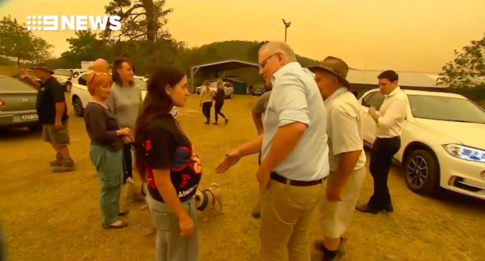 Pictured is a frustrated woman refusing to shake Scott Morrison's hand.