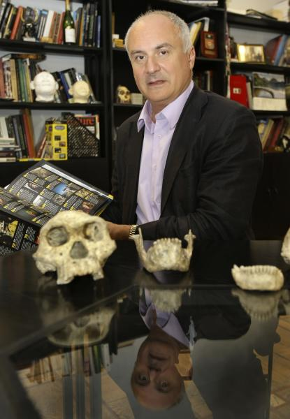 In this photo taken Oct. 2, 2013, David Lordkipanidze, director of the Georgia National Museum, displays the ancient skull and jaws of a pre-human ancestor at the National Museum in Tbilisi, Georgia, Wednesday, Oct. 2, 2013. The discovery of a 1.8-million-year-old skull of a human ancestor found below Dmanisi, a medieval Georgian village, captures early human evolution on the move in a vivid snapshot and indicates our family tree may have fewer branches than originally thought, scientists say. (AP Photo/Shakh Aivazov)