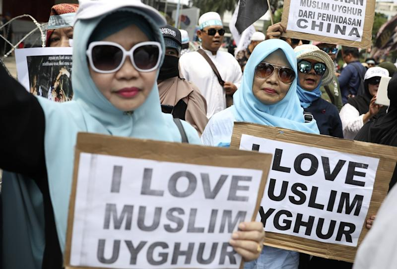 """Muslim women outside the Chinese Embassy in Jakarta, Indonesia, hold posters with the words """"I love Muslim Uyghur."""""""