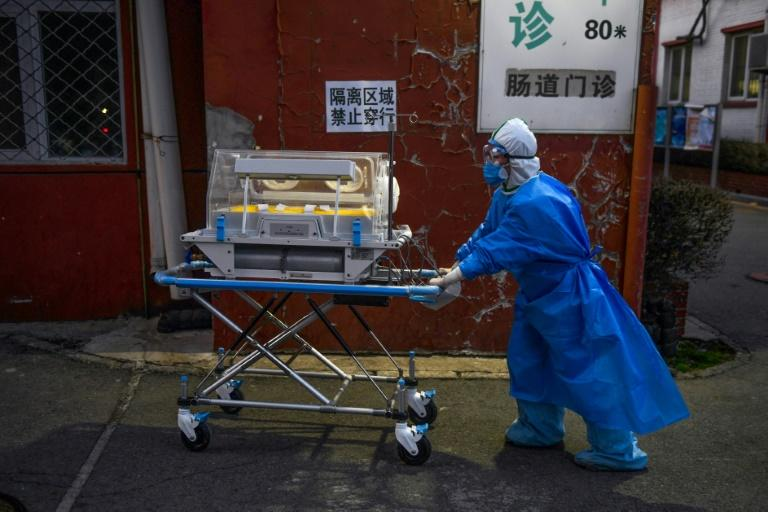 A medical worker wearing protective clothing against the new coronavirus pushes an incubator between buildings at a hospital in Beijing on February 21