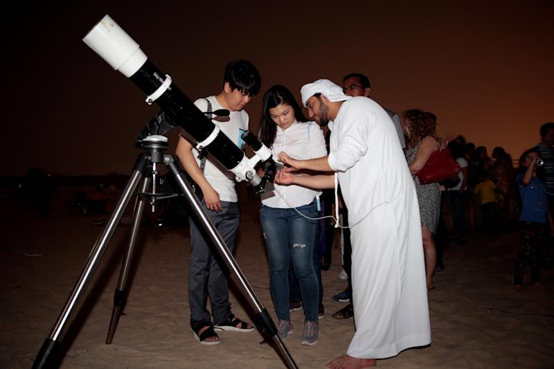 "An Emirati man uses a telescope to take a picture of the lunar eclipse of a full ""Blood Moon"" at Al Sadeem Observatory in Al Wathba near Abu Dhabi. (Christopher Pike / Reuters)"