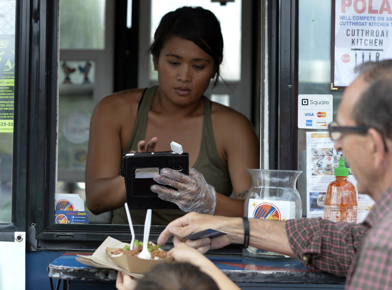 DENVER, CO - JUNE 18: Kathy Poland of Taste of the Philippines swipes uses square system for her transactions June 18, 2015 at Civic Center Park. Food truck vendors set up for the afternoon lunch crowd at Civic Center Park. How are small businesses and entrepreneurs that use credit card readers like Square that attach to their phone or tablet handling the Oct. 1 deadline to have card readers that can handle cards with microchips. Among those affected are food truck operators. (Photo By John Leyba/The Denver Post via Getty Images)