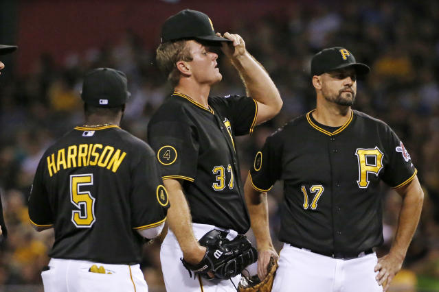 Pittsburgh Pirates relief pitcher Justin Wilson, center, waits with teammates Josh Harrison (5) and Gaby Sanchez (17) before being removed from the baseball game by manager Clint Hurdle during the eighth inning against the Miami Marlins in Pittsburgh Tuesday, Aug. 5, 2014. The Marlins scored five runs in the eighth. (AP Photo/Gene J. Puskar)