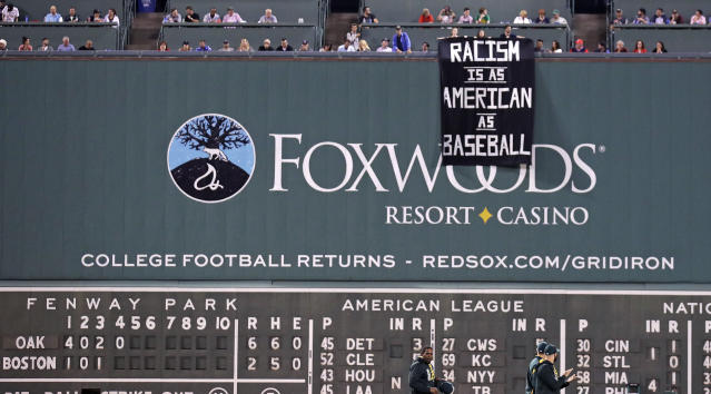 "Protesters unfurled a sign at a Red Sox game last week that read, ""Racism is as American as baseball."" (AP)"