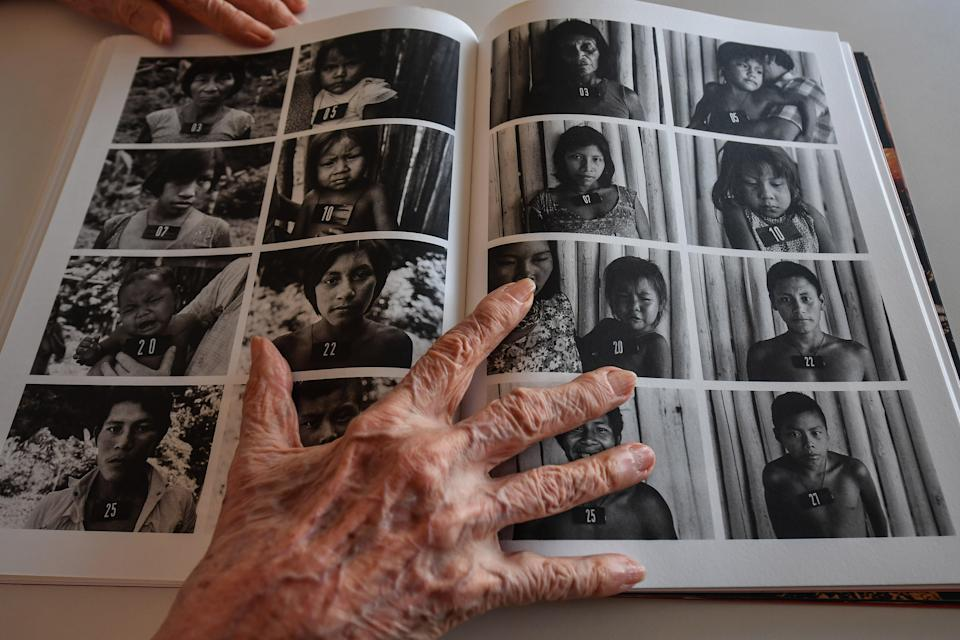 Claudia Andujar keeps a book open on a page with portraits of indigenous peopleAFP via Getty