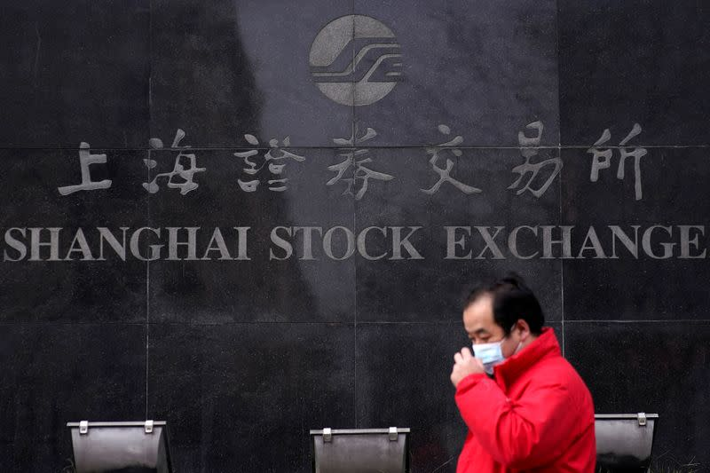FILE PHOTO: A men wearing a mask walk at the Shanghai Stock Exchange building at the Pudong financial district in Shanghai