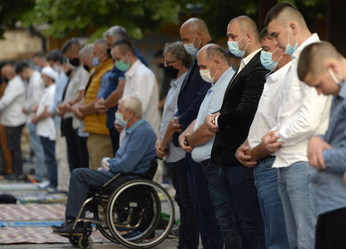 Worshippers wearing masks to help stop the spread of the coronavirus, offer Eid al-Adha prayer in front of the Gazi Husrev-beg mosque in Sarajevo, Bosnia, Friday, July 31, 2020. Eid al-Adha, or Feast of Sacrifice, Islam's most important holiday, marks the willingness of the Prophet Ibrahim to sacrifice his son. (AP Photo/Kemal Softic)