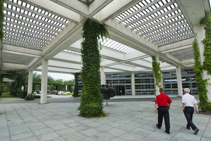 People walk through a partially covered courtyard at the Cummins corporate offices in Columbus, Ind.
