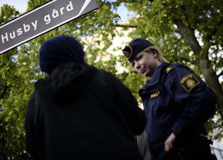 A Sweden policewoman speaks with a resident of Husby on May 22, 2013. Rioters have torched cars and attacked local police stations in 15 immigrant-populated Stockholm suburbs in a fourth night of riots, shattering Sweden's image as a peaceful and egalitarian nation