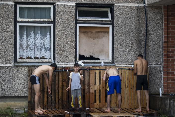 Migrants from Iraq bath at the refugee camp in the village of Verebiejai, some 145km (99,1 miles) south from Vilnius, Lithuania, Sunday, July 11, 2021. Migrants at the school in the village of Verebiejai, about 140 kilometers (87 miles) from Vilnius, haven't been allowed to leave the premises and are under close police surveillance. Some have tested positive for COVID-19 and have been isolated in the building. (AP Photo/Mindaugas Kulbis)