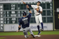 Houston Astros shortstop Carlos Correa, right, throws to first for a double play as Tampa Bay Rays' Mike Zunino (10) slides into second base during the seventh inning of a baseball game Tuesday, Sept. 28, 2021, in Houston. Tampa Bay Rays' Kevin Kiermaier was out at first and Zunino was out at second on the double play. (AP Photo/David J. Phillip)