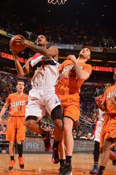 PHOENIX, AZ - JANUARY 24: Trevor Ariza #1 of the Washington Wizards drives to the basket against Miles Plumlee #22 of the Phoenix Suns on January 24, 2014 at U.S. Airways Center in Phoenix, Arizona. (Photo by Barry Gossage/NBAE via Getty Images)