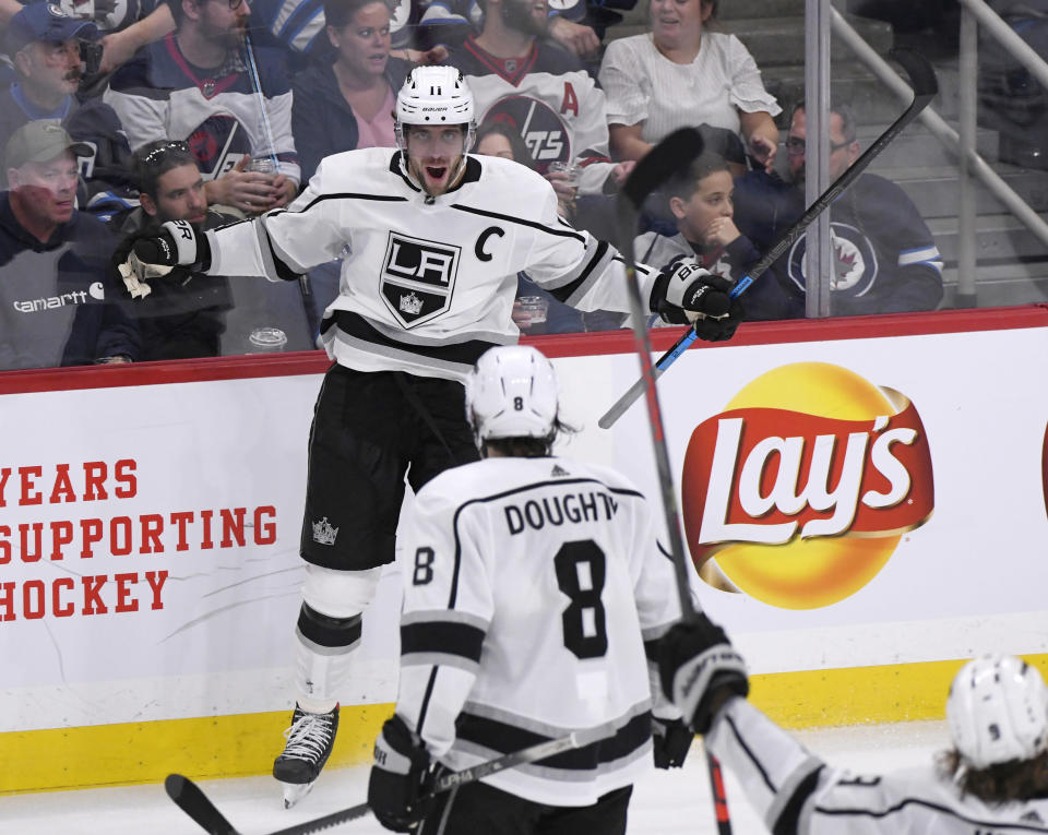 Los Angeles Kings' Anze Kopitar (11) celebrates his goal against the Winnipeg Jets with Drew Doughty (8) during the third period of an NHL hockey game Tuesday, Oct. 22, 2019, in Winnipeg, Manitoba. (Fred Greenslade/The Canadian Press via AP)