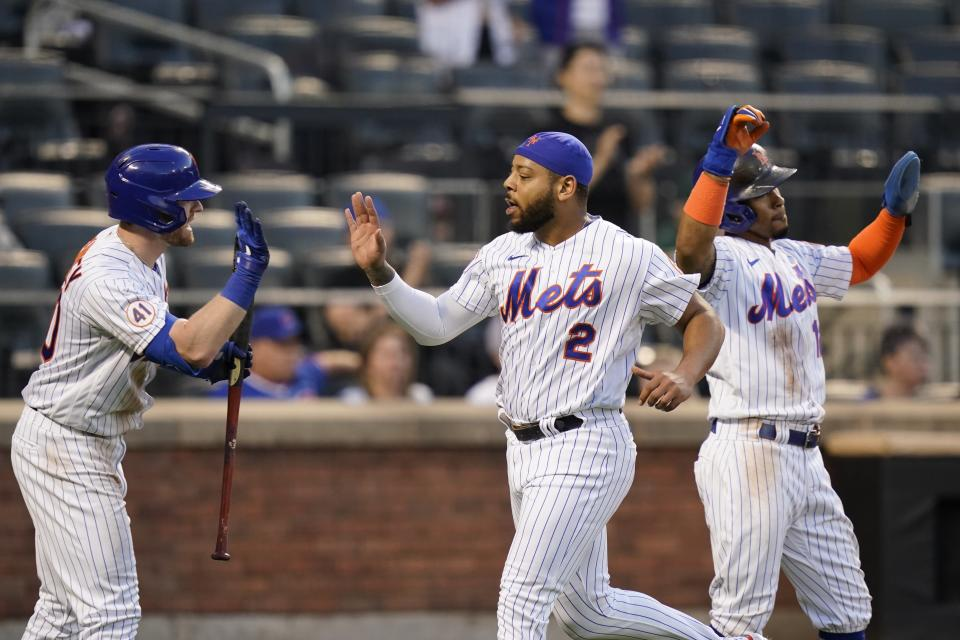 New York Mets' Dominic Smith (2) celebrates with Billy McKinney, left, and Francisco Lindor after scoring on a two-run single by Pete Alonso during the third inning of the team's baseball game against the Chicago Cubs on Tuesday, June 15, 2021, in New York. (AP Photo/Frank Franklin II)