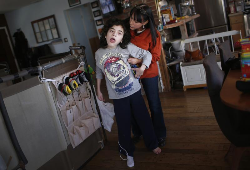 Missy Miller (R) holds her epileptic son Oliver in their home at Atlantic Beach, New York January 7, 2014. Oliver suffered a brain stem injury in utero and now, at 14, has hundreds of seizures a day. For months, his family has pinned their hopes on a strain of marijuana developed in Colorado that has helped children with similar conditions. But under an executive order by Governor Andrew Cuomo on Wednesday making New York the 21st state to allow medical marijuana, it will remain illegal to grow marijuana or to import specialized plants from other states. Patients will have little say in the marijuana they are prescribed and people like Oliver - who could benefit from a specialized strain known as Charlotte's Web that is high in the compound cannabidiol, or CBD, - would be cut out entirely. Picture taken January 7, 2014. REUTERS/Mike Segar (UNITED STATES - Tags: HEALTH POLITICS)