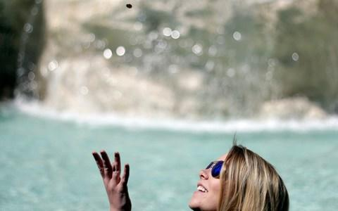 A woman tosses a coin into the Trevi fountain in Rome. Legend has it that tossing a coin over one's shoulder into the fountain ensures a return visit - Credit: Gregorio Borgia/AP