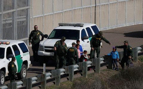 U.S. Border Patrol agents after crossing illegally over the border wall into San Diego, California - Credit: Rebecca Blackwell/AP