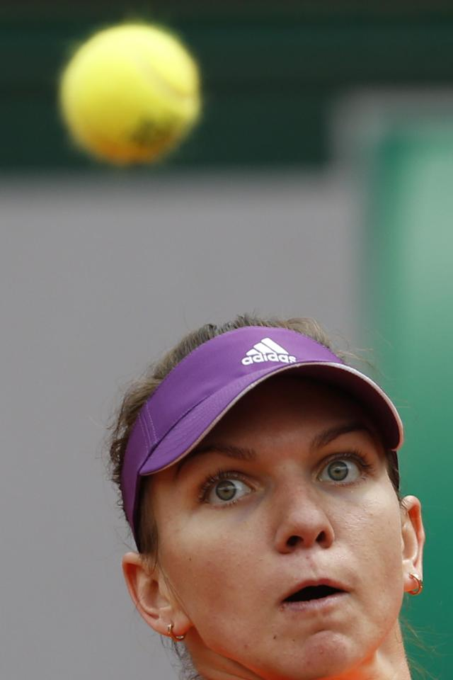Romania's Simona Halep returns the ball during the fourth round match of the French Open tennis tournament against Sloane Stephens of the U.S. at the Roland Garros stadium, in Paris, France, Monday, June 2, 2014. (AP Photo/Darko Vojinovic)