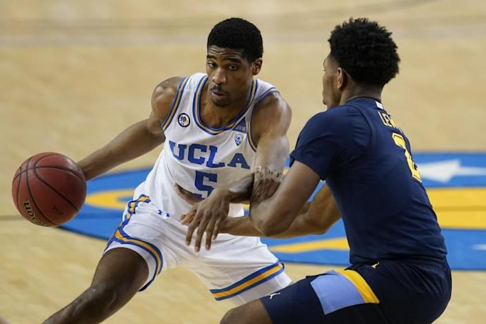 UCLA guard Chris Smith, left, is defended by Marquette forward Justin Lewis during the second half of an NCAA college basketball game Friday, Dec. 11, 2020, in Los Angeles. (AP Photo/Ashley Landis)