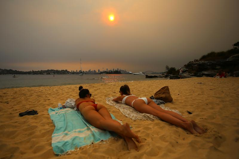 Two sunbathers in bikinis on Milk Beach in Vaucluse on Saturday. Source: AAP