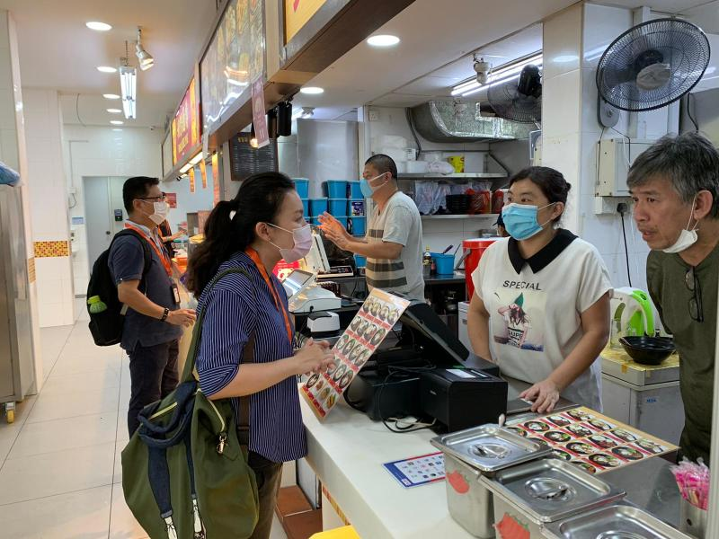 Safe Distancing and SG Clean ambassadors speaking to hawkers during the elevated safe distancing period to curb the spread of COVID-19. (PHOTO: Facebook/Masagos Zulkifli)