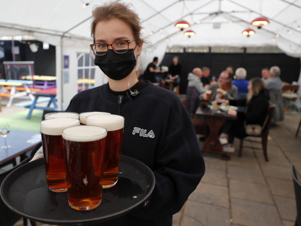 A waitress carries beer pints at the outdoor space under the marquee of the Black Lion pub in London, Monday, April 12, 2021. Millions of people in England will get their first chance in months for haircuts, casual shopping and restaurant meals on Monday, as the government takes the next step on its lockdown-lifting road map.(AP Photo/Frank Augstein)