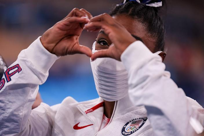 Simone Biles flashes the heart sign to a fan