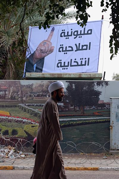 """In this Wednesday, Feb. 21, 2018, photo, a Shiite cleric passes a poster reading """"Electoral reform"""" in Baghdad. Iraq's Shiites, Sunnis and Kurds have grown more fragmented and divided ahead of the national elections scheduled for May due to deep differences among each group that have spawned more and smaller alliances seeking to have a bigger share in the new parliament. (AP Photo/Hadi Mizban)"""