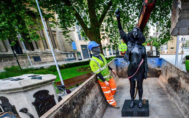 The statue, entitled A Surge of Power (Jen Reid) 2020, is removed from the plinth and loaded into a recycling and skip hire lorry by contractors - PA