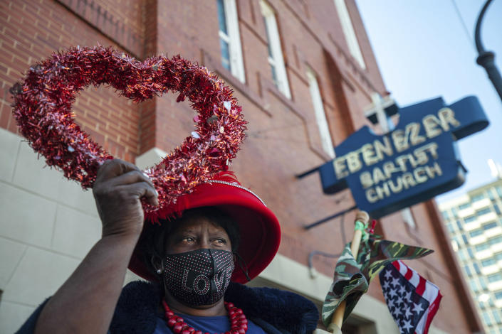 G.A. Breedlove holds up a heart outside of the historic Ebenezer First Baptist Church where Martin Luther King Jr. preached on Monday, Jan. 18, 2021, in honor of Martin Luther King Jr. Day, in Atlanta. (AP Photo/Branden Camp)