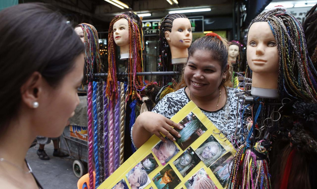 A hairstylist shows braid samples to a woman at an outdoor beauty parlour in a tourist district of Khao San Road in Bangkok May 27, 2014. The Thai army's imposition of martial law is another blow to the country's tourist industry, adding to the economic pain from six months of destabilising street protests as airlines cut back on flights and concern over insurance adds to travellers' worries. Tourism makes up about 10 percent of Thailand's economy and the ebbing number of visitors contributed to a fall in gross domestic product in the first three months of the year, adding to fears the country is sliding into recession. REUTERS/Erik De Castro (THAILAND - Tags: POLITICS CIVIL UNREST BUSINESS TRAVEL)