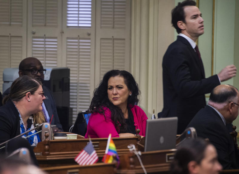 Assemblywoman Lorena Gonzalez, D-San Diego, talks with other assembly members on the Assembly floor at the Capitol in Sacramento, Calif., on Thursday, Feb. 27, 2020, as Assemblyman Kevin Kiley, R-Rocklin, walks past her. Gonzalez has proposed an amendment to Assembly Bill 5 — which requires many independent contractors to be re-classified as employees with benefits — that removes the submission cap but also mandates that freelancers cannot replace regular employees. (Daniel Kim/The Sacramento Bee via AP)