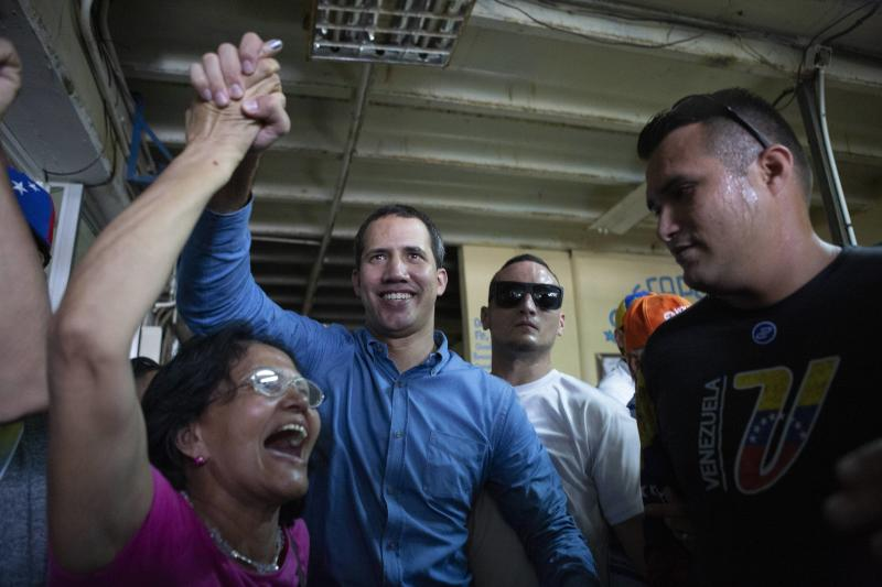 Venezuela's opposition leader and self-proclaimed Interim President Juan Guaido, center, greets merchants at the Free Market in Maracay, Aragua's State, Saturday, August 31, 2019. Venezuelan officials say they have proof of paramilitary training camps operating in neighboring Colombia where groups are plotting attacks to undermine President Nicolas Maduro. (AP Photo/Andrea Hernandez)