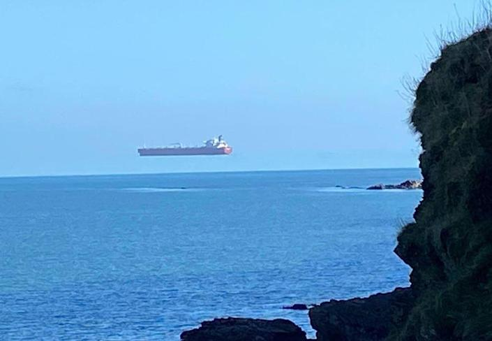 A ship appears to hover over the sea off the coast of Cornwall, England, in a photo captured by David Morris that shows the optical illusion known as