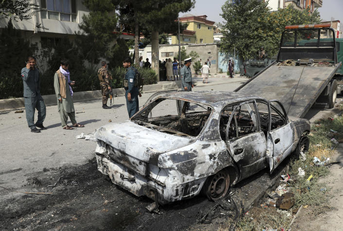 Security personnel inspect a damaged vehicle where rockets were fired from in Kabul, Afghanistan, Tuesday, July 20, 2021. At least three rockets hit near the presidential palace on Tuesday shortly before Afghan President Ashraf Ghani was to give an address to mark the Muslim holiday of Eid-al-Adha. (AP Photo/Rahmat Gul)