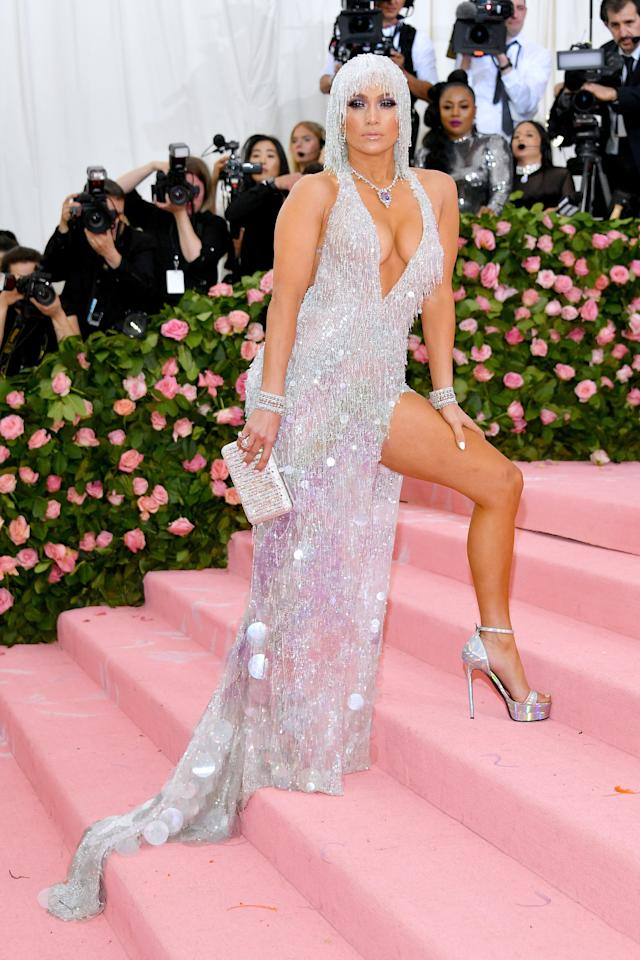 <p>It was a power pose — and a whole lot of sparkle! — for the 2019 Met Gala Celebrating Camp: Notes on Fashion. J.Lo wore a silver, fringed Versace gown with a plunging neckline.</p>
