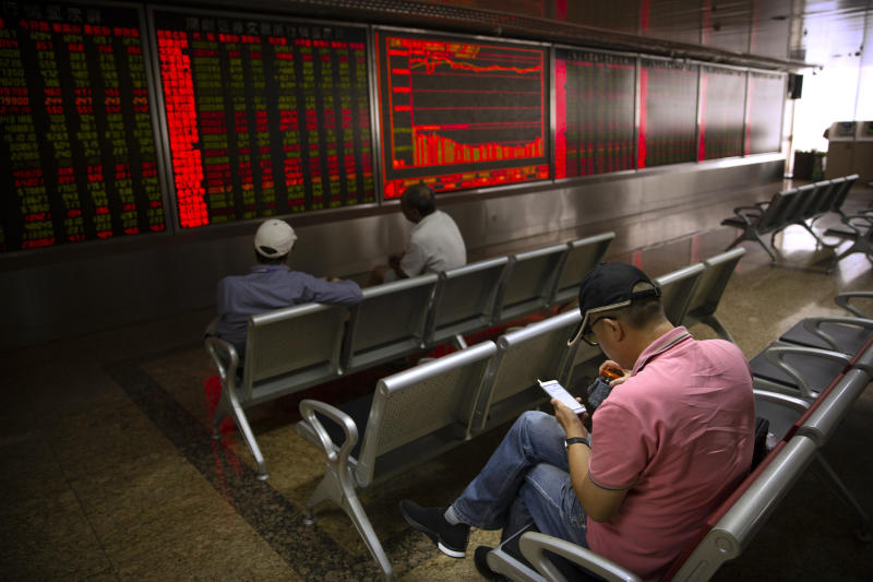 A Chinese investor uses his smartphone as he monitors stock prices at a brokerage house in Beijing, Wednesday, Sept. 11, 2019. Asian shares were mostly higher Wednesday, cheered by a rise on Wall Street amid some signs of easing tensions between the U.S. and China on trade issues. (AP Photo/Mark Schiefelbein)