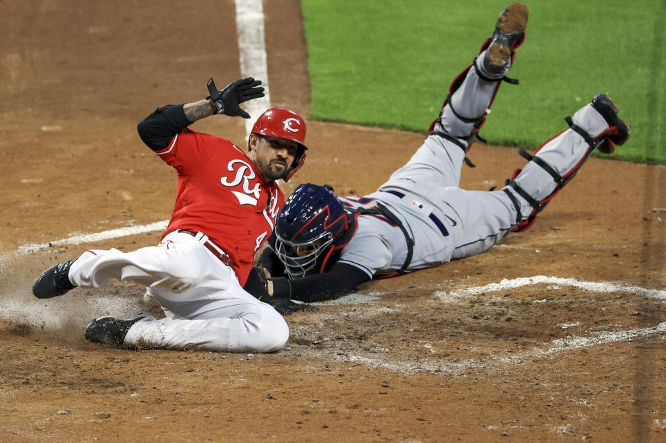 Cincinnati Reds' Nick Castellanos, left, slides into home plate safely ahead of the tag from Cleveland Indians' Roberto Perez, right, on a two-run RBI double by Cincinnati Reds' Eugenio Suarez, during the third inning of a baseball game in Cincinnati, Friday, April 16, 2021. (AP Photo/Aaron Doster)