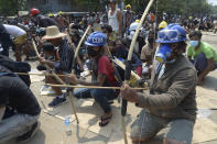 FILE - In this March 27, 2021, file photo, anti-coup protesters prepare makeshift bow and arrows to confront police in Thaketa township Yangon, Myanmar. The military takeover of Myanmar early in the morning of Feb. 1 reversed the country's slow climb toward democracy after five decades of army rule. But Myanmar's citizens were not shy about demanding their democracy be restored. (AP Photo, File)