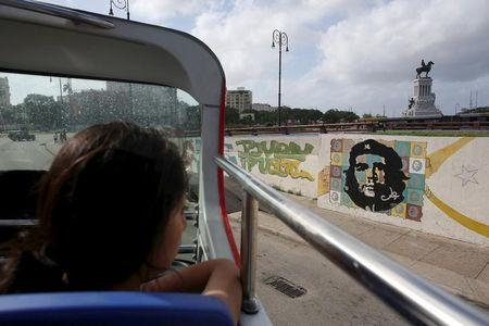 """A tourist from Peru looks at a graffiti of revolutionary hero Ernesto """"Che"""" Guevara from the top of a double decker sightseeing bus in Havana"""