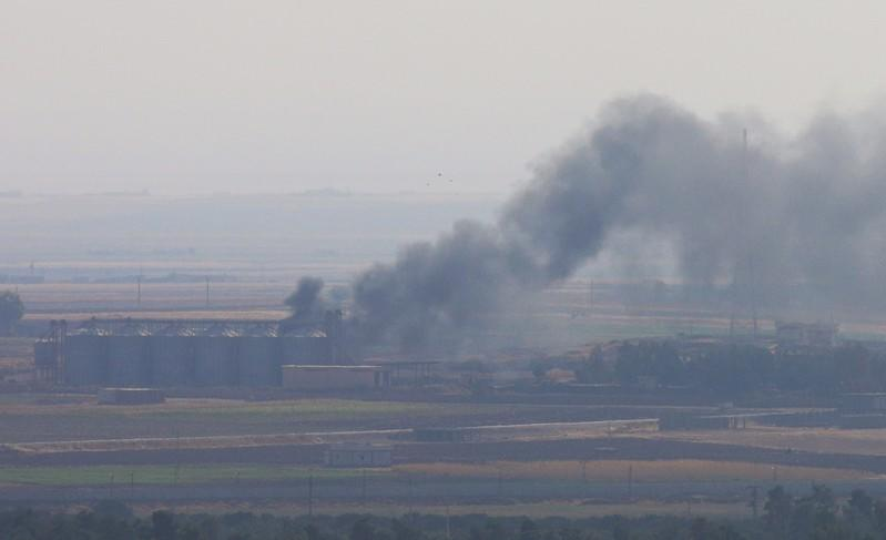FILE PHOTO: Smoke rises from a building near the Syrian town of Ras al-Ain as seen from the Turkish border town of Ceylanpinar